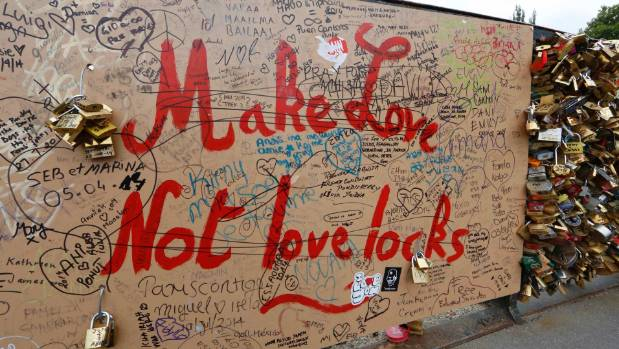 "A panel with the message, ""Make Love, not love locks"" is seen of the Pont de l'Archeveche bridge, near the Notre Dame ..."