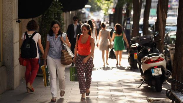 Members of the public walk past the affluent shopping street of Calle de Serrano, Madrid.