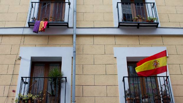 A Spanish Monarchist flag (R) flutters close to pieces of cloth hanging as a Republican flag (L) on two floors of a ...