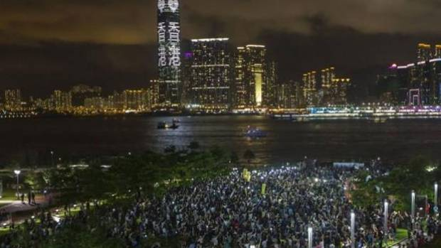 PROTEST: Pro-democracy protesters hold up their mobile phones during a campaign to kick off the Occupy Central civil ...