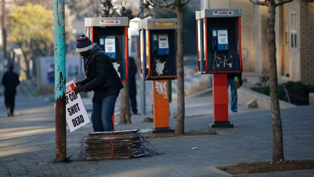 A worker hangs posters displaying newspaper headlines next to public phone booths in Lesotho's capital of Maseru on Sunday.