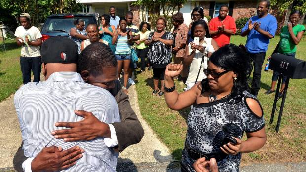 Geraldine Brown, right, fights back tears as her brothers Leon Brown, left, and Henry McCollum greet each other in the ...