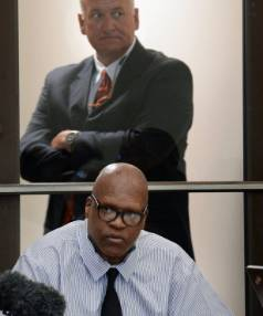 Prosecutor Johnson Britt stands behind Leon Brown during a break in the proceedings on Tuesday.