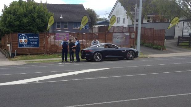 HANDCUFFED: Phil Rudd talking to police in Tauranga. He was later placed in a police car.