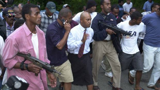 COUP LEADER: Fijian nationalist George Speight, flanked by armed gunmen, removes road blocks around the Parliament ...