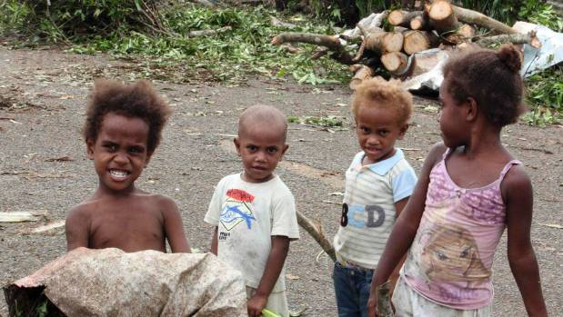 Children stand in front of debris on a street near their homes in Port Vila.
