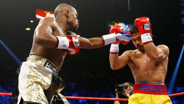 Floyd Mayweather Jr throws a straight left hand as his Filipino rival Manny Pacquiao raises his guard.