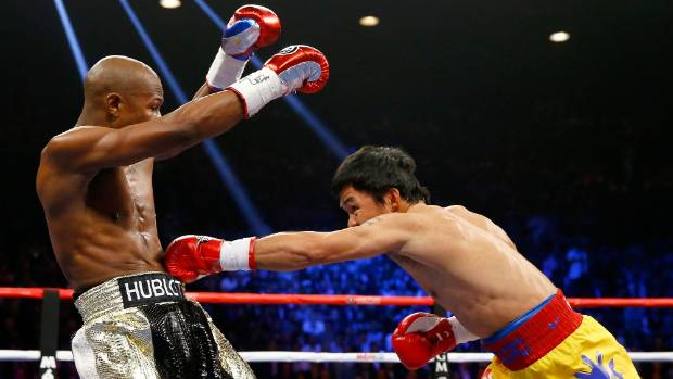 Manny Pacquiao lands a left to body as his American opponent Floyd Mayweather retreats to the ropes.
