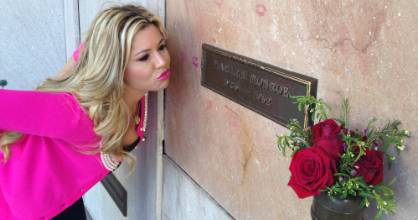 A tourist plants a kiss on the headstone of Marilyn Monroe at Pierce Brothers Cemetery in Los Angeles, a stop on the Dearly Departed Hollywood bus tour.