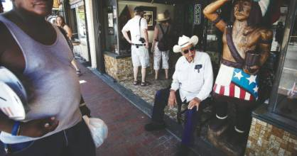 Don Pedro Bello Sr., from a long tradition of tobacconists, sits on a chair in front of his Cuba Tobacco Cigar store on the street known as Calle Ocho in Little Havana.