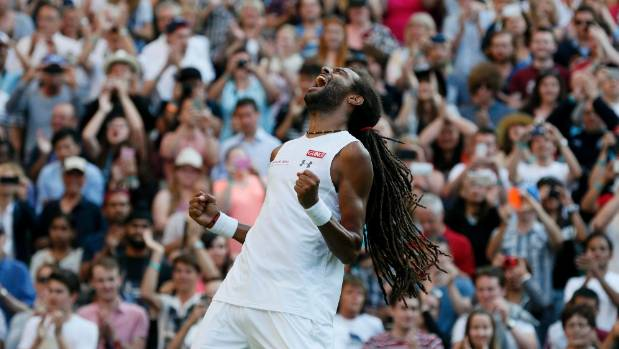 Dustin Brown celebrates after beating two-time champion Rafael Nadal in the second round at Wimbledon.