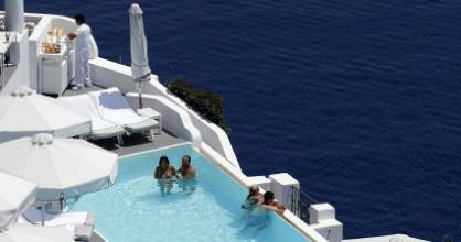 Tourists relax in a private swimming pool in the village of Oia on the Greek island of Santorini, Greece, July 1, 2015. Greek Prime Minister Alexis Tsipras has written to international creditors saying Greece could accept their last bailout offer if some conditions were changed, but Germany expressed scepticism while saying the door was still open for negotiations. REUTERS/Cathal McNaughton