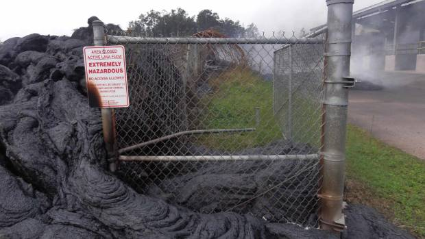 Lava from the volcano oozes around a fence at the Pahoa transfer station last November.