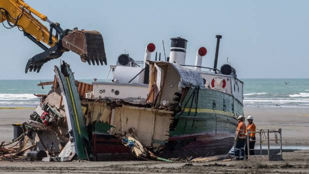 The historic ship MV Tuhoe is pulled apart at the mouth of the Waimakariri River.