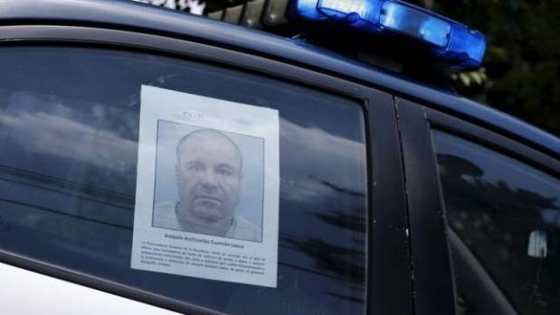 A police vehicle is seen a poster with a photo of drug lord Joaquin ''El Chapo'' Guzman offering a reward of 60 million ...
