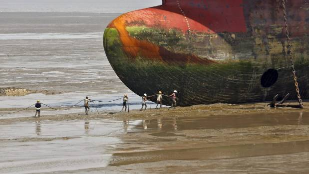 Workers carry a rope line to fasten a decommissioned ship at the Alang shipyard in Gujarat, India.