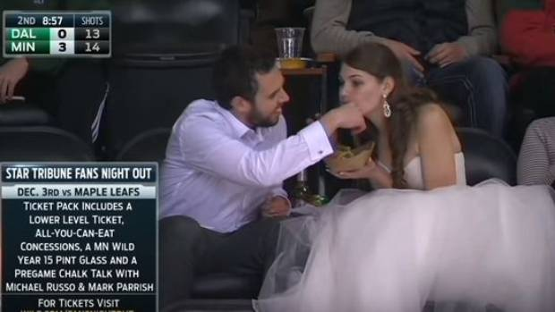 True love looks like a man wiping cheeseburger juice from his bride's chin at an ice hockey game.