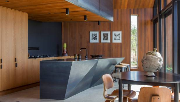 Timber veneer and blue steel combine in the Grand Designs Pakiri house designed by architect Paul Clarke. Black accents in the house include several painted walls, furniture, light fixtures and tapware.