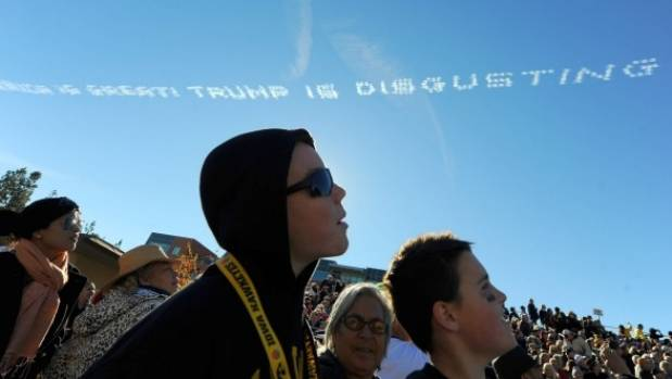 "Parade spectators watch as airplane sky writers write a message ""America is great! Trump is disgusting"" above the route ..."
