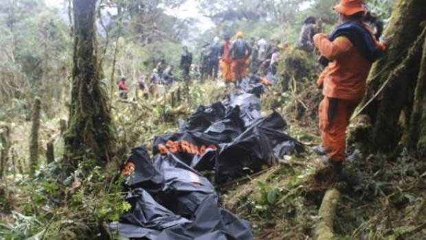 A rescue team member stands near bodies of the victims of the crashed Trigana Air plane, at the crash site near Oksibil, ...
