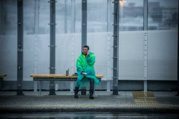 A man shelters from the rain in a bus stop on Auckland's K Road.