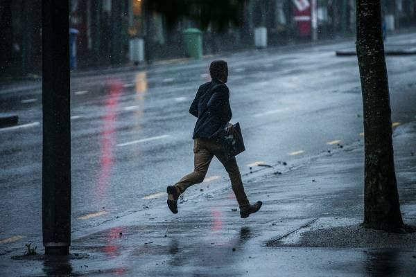 A man dashes for cover from the rain in Central Auckland.