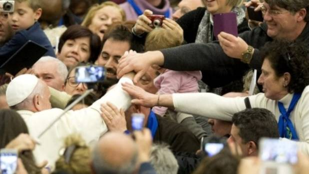 Pope Francis is mobbed by the faithful as he arrives at the Vatican.