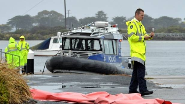 A police boat recovers three bodies after a plane crash in Barwon Heads, near Geelong, Australia.