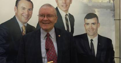 Apollo 13 astronaut Fred Haise beside a picture of his younger self (extreme right) and the rest of his crew
