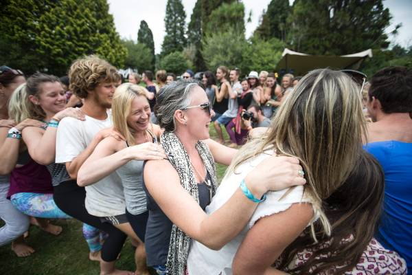 A large group of festival goers join in on the circle love hug.