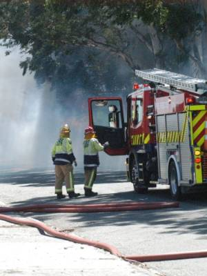 Firefighters battle a grass and vehicle fire at the corner of Tremaine Ave and Midhurst St in Palmerston North.
