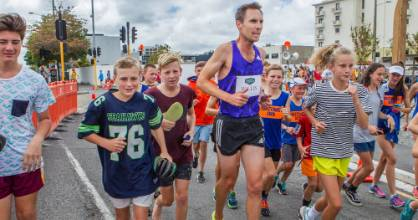 Olympian Nick Willis is joined by children on his warm-down lap after winning the street mile race during an athletics event held in central Christchurch.