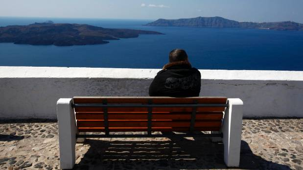 A local rests on a bench atop the caldera at the volcanic island of Santorini.