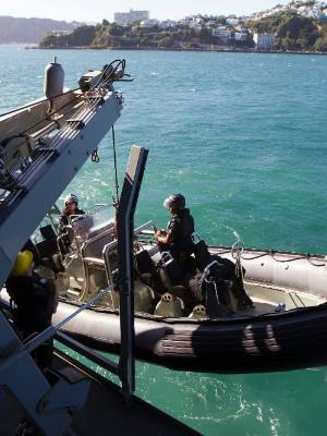 Navy personnel  hoist their inflatable boat aboard the Canterbury before berthing at Queens Wharf.