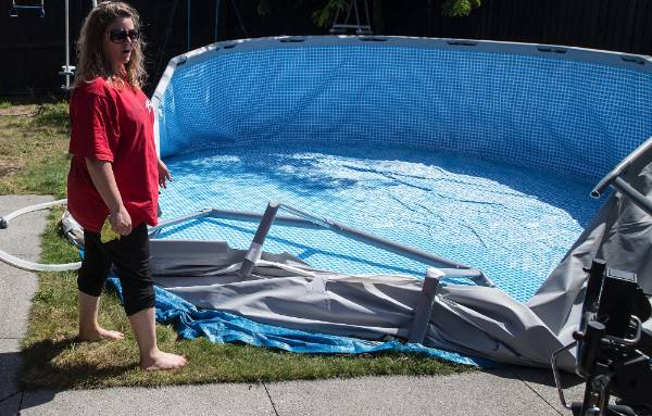Tina Bell at her house on Linkwater Way in Parklands with a pool that broke in the earthquake.