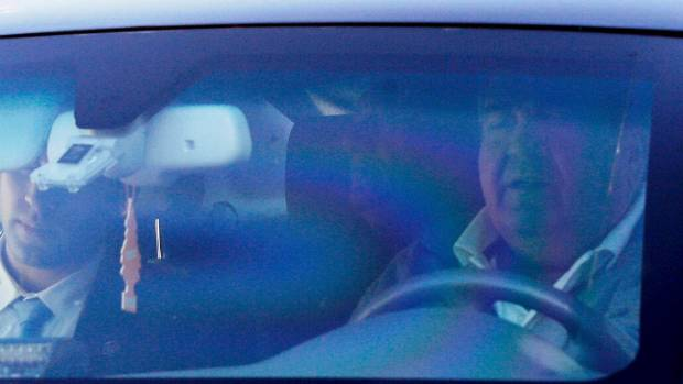 Former Israeli Prime Minister Ehud Olmert (right) is seen inside a car as he leaves his house in Jerusalem.