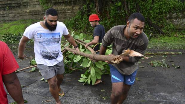 Fijian men clear debris in the capital Suva after Cyclone Winston swept across Viti Levu Island.