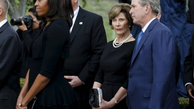 Former President George W Bush and his wife Laura wait to pay their respects with first lady Michelle Obama during the ...