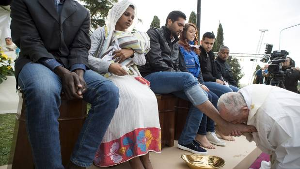 Pope Francis kisses the foot of a refugee during the foot-washing ritual at the Castelnuovo di Porto refugees center ...