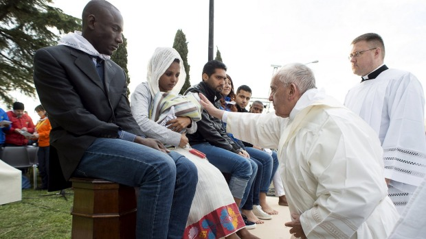 Pope Francis blesses a baby during the foot-washing ritual. Pope Francis  washed and kissed the feet of refugees, ...