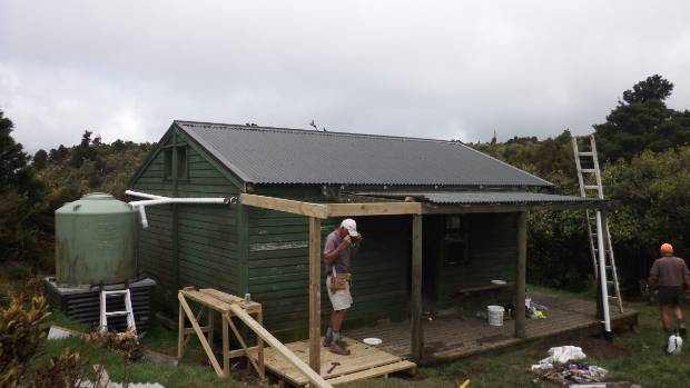 Kaimai Ridgeway Trust volunteers working on a neglected hut in the Kaimai Ranges.