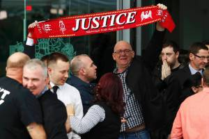 Relatives hold up a scarf after the jury delivered its verdict of unlawful killing at the new inquests into the ...