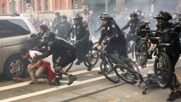 Police officers detain a protester during anti-capitalist in Seattle.