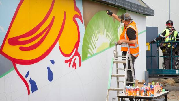 Street artist Dcypher creating the Kiwiana-themed mural on the Wharenui Recreation Centre, which reopens on Friday.