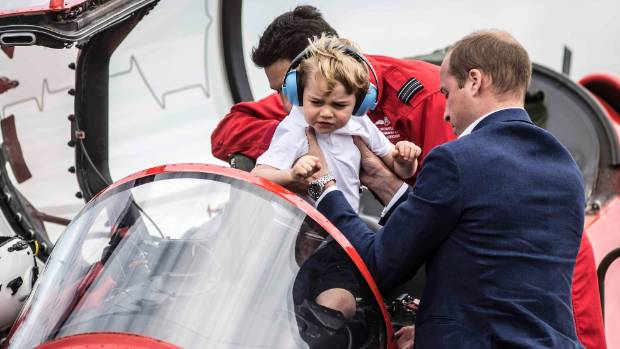 Prince George is lifted out of the cockpit of a red arrows plane by his father.
