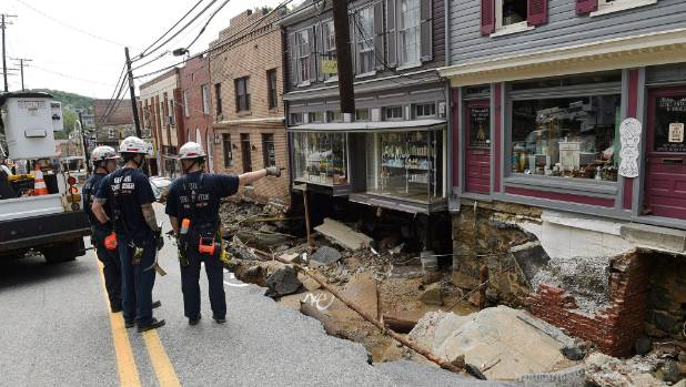 Rescue workers on Sunday look at the destruction caused by a flash flood along Main Street in Ellicott City.