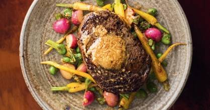 Aged beef steak with miso butter, broad beans, carrots and radishes.