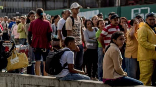 A man waits in line to buy food at a grocery store in La Urbina, east Caracas, Venezuela.