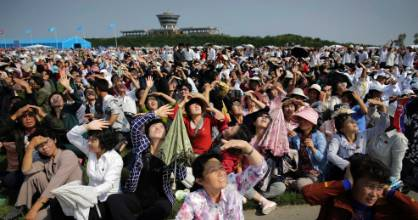 North Koreans shield their eyes from the sun as they watch an aerial display in Wonsan, North Korea.