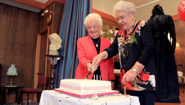Joan Sutherland and Anne Jennings cut the cake at The Southland Women's Club 95th anniversary celebrations.